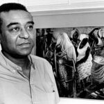 John T. Biggers stands next to one of his murals
